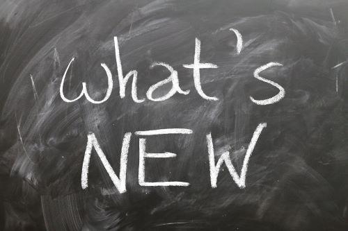 """Tafel, auf der mit weißer Kreise """"what's NEW"""" steht"""