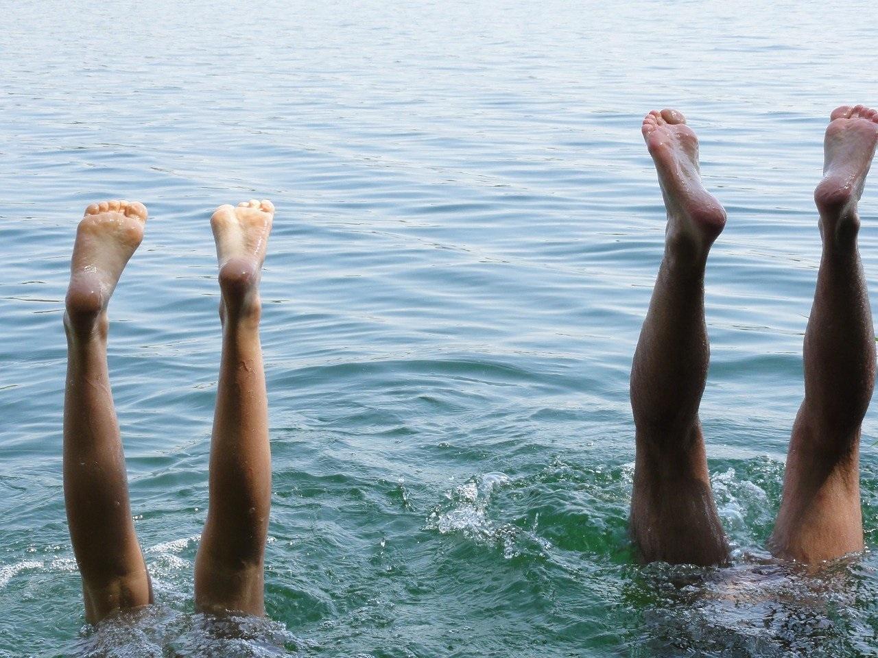 zwei paar Beine ragen aus dem Wasser. Kopfstand im Badesee